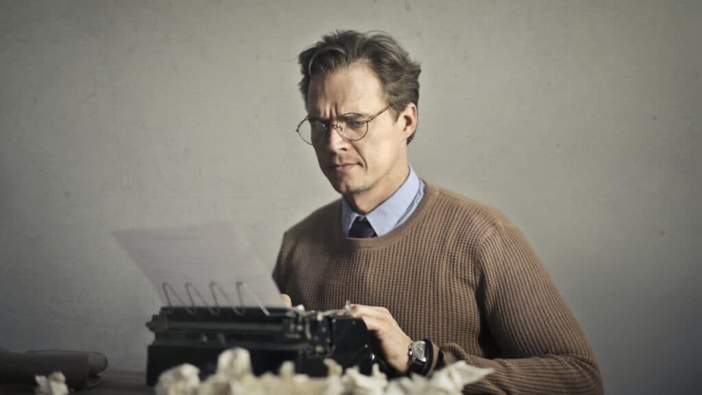 Image of man typing on a typewriter