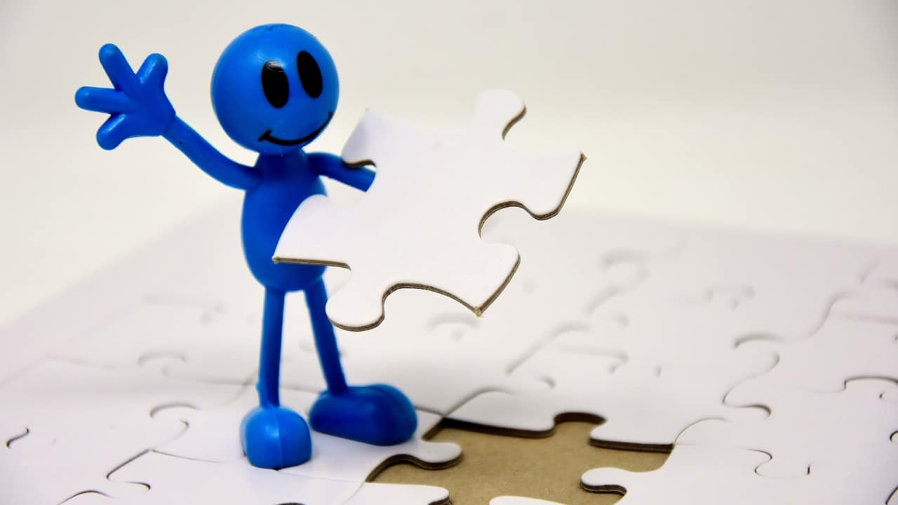 Image of a figure adding a jigsaw puzzle piece
