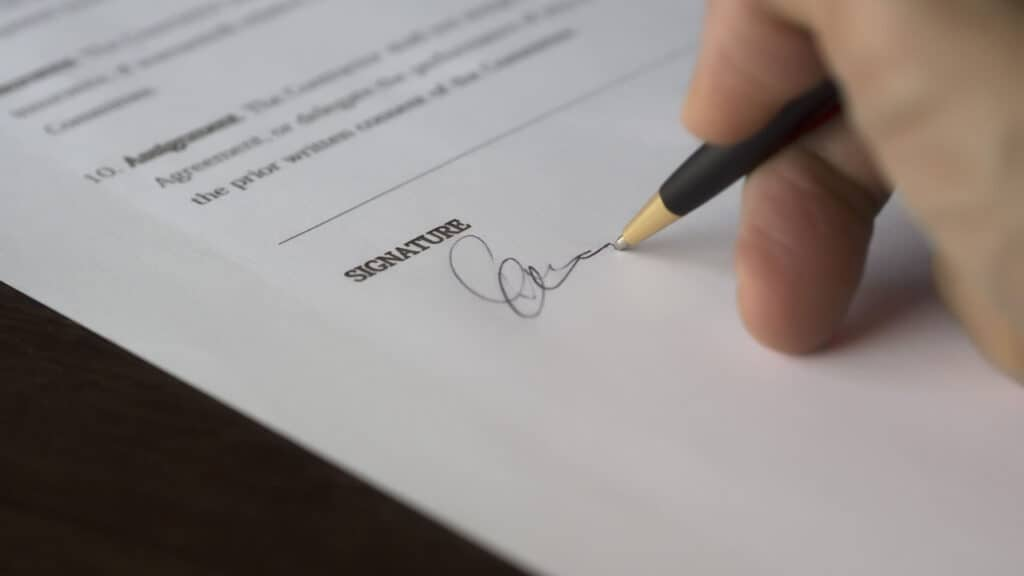 Image of a man signing a form